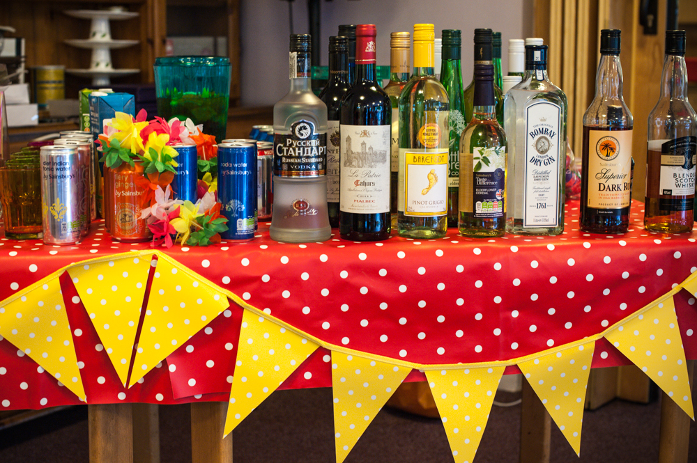Table set up as a bar of drinks with decorations