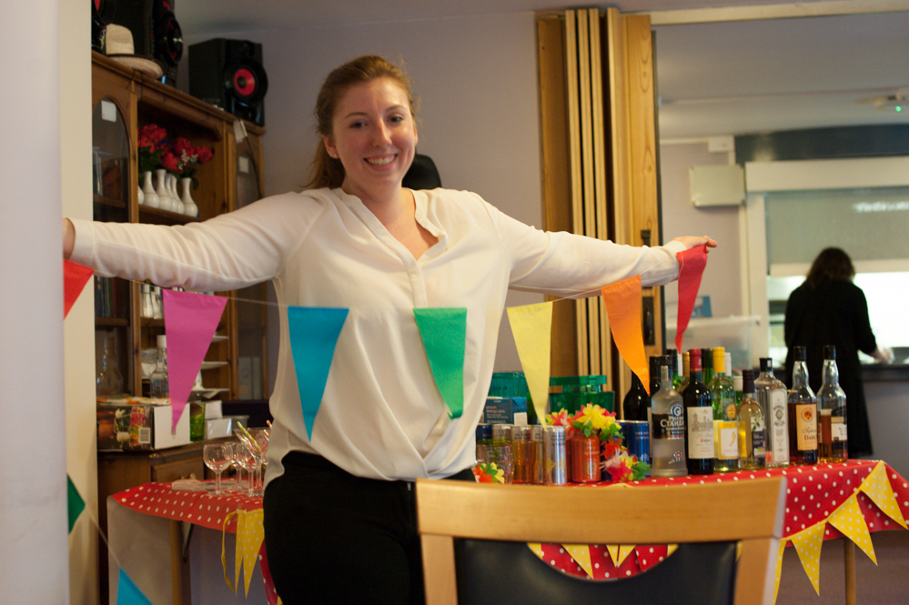 Volunteer smiling with a string of rainbow bunting