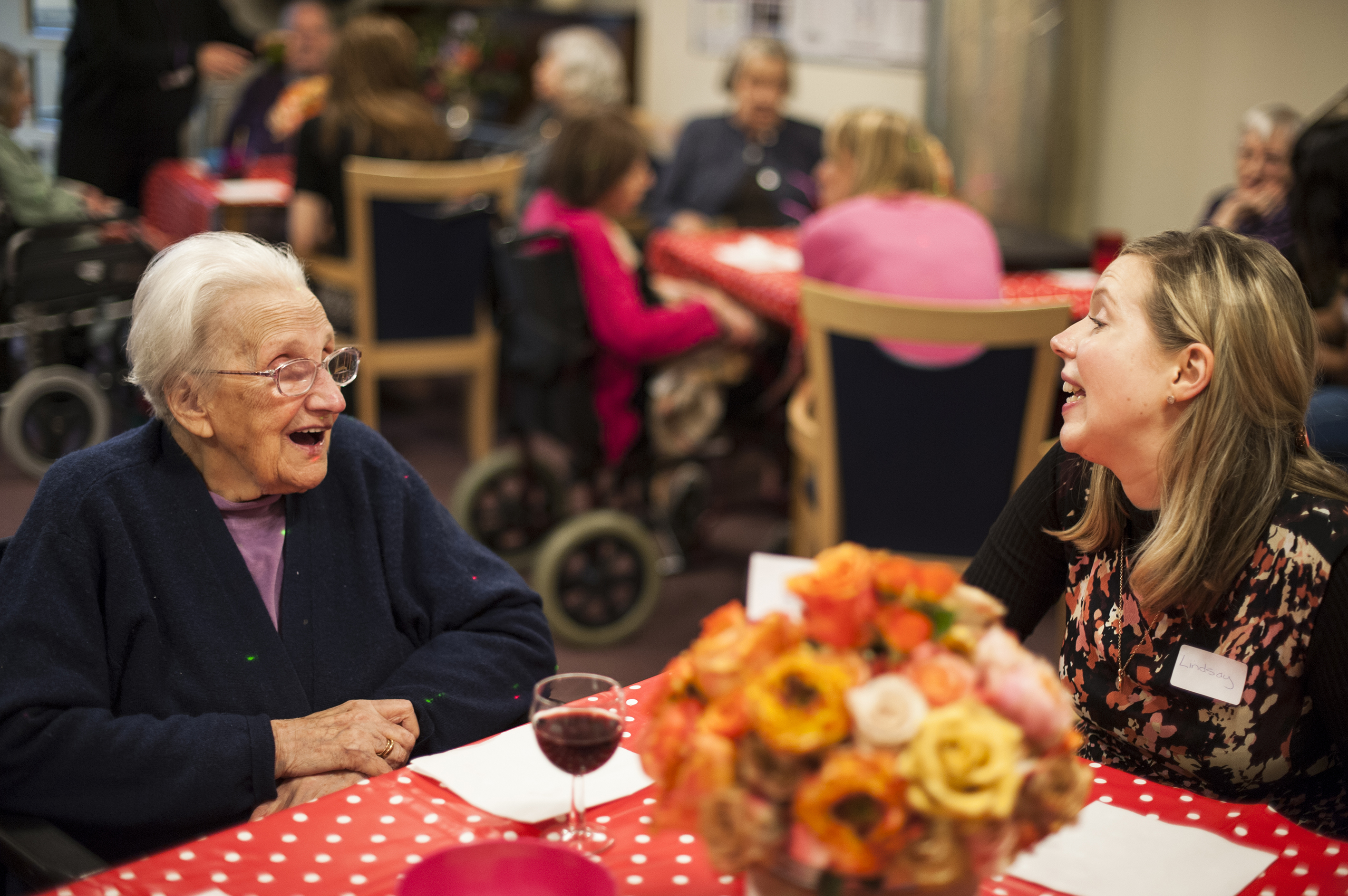 Happy female resident & volunteer chat with orange flowers on table