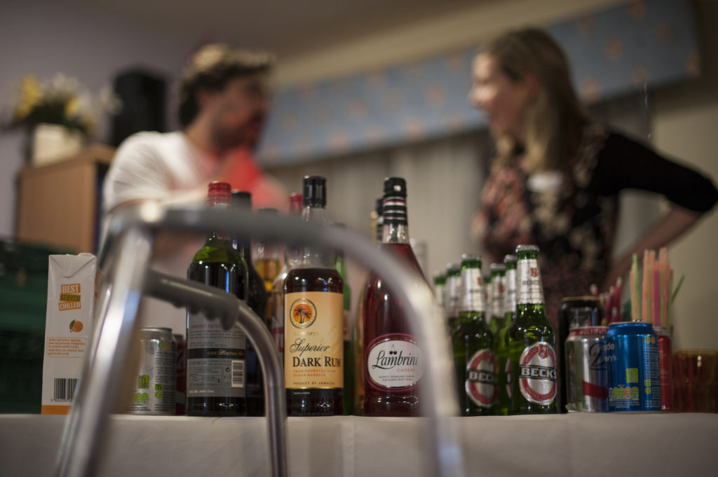 Row of drinks on table with a zimmer frame in front and two volunteers behind